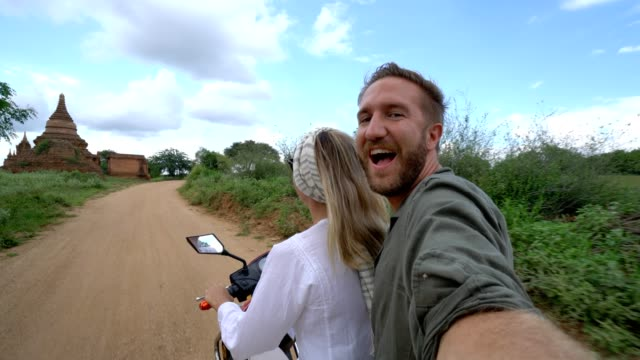 Couple travelling exploring ancient temple area in Myanmar taking selfies on the go. Adventure selfies point of view Young couple on a electric bike in Asia take selfies. Couple travelling exploring ancient temple area in Myanmar taking selfies on the go. Adventure selfies point of view bagan stock videos & royalty-free footage