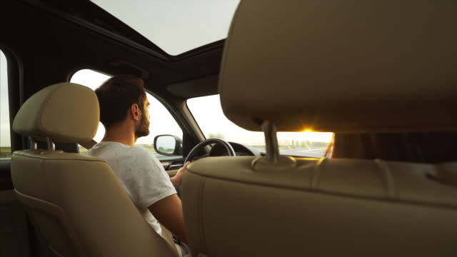Couple travelling. Young couple travelling at sunset. They are on the road in a beautiful sunny day. luxury car stock videos & royalty-free footage
