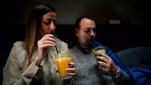 Couple trying new tastes Young couple drinking fresh juices at cafe. straw stock videos & royalty-free footage