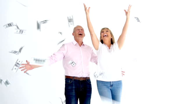 Couple trying to grab money falling from the sky on slow motion video