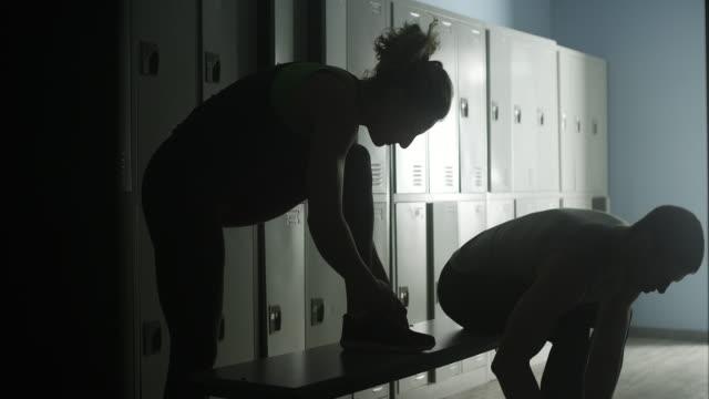 coppia legando scarpe da ginnastica nello spogliatoio - annodare video stock e b–roll