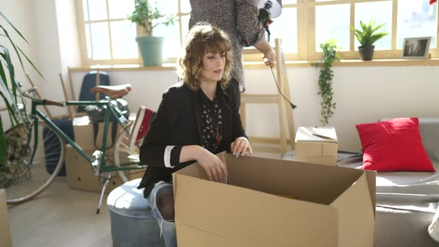 Couple unpacking boxes in new home