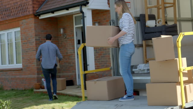 Couple Unpacking Moving In Boxes From Removal Truck video
