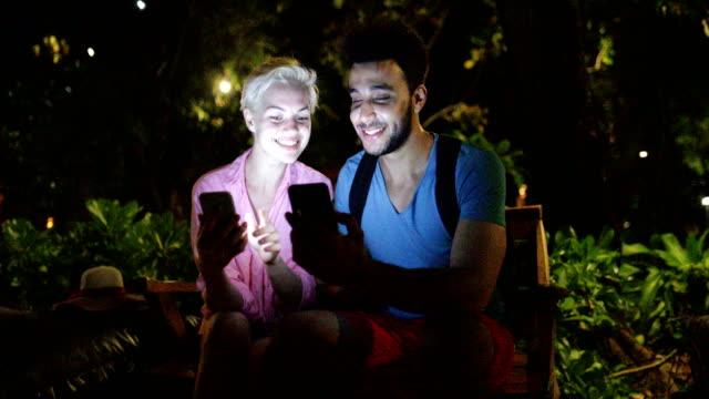 夜の公園、人および女性の屋外のオンライン チャットでベンチに座っているスマートの携帯電話を使用してカップルを受け入れる - ベンチ点の映像素材/bロール