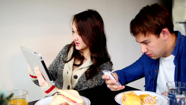 Couple using digital tablet and mobile phone while having breakfast video