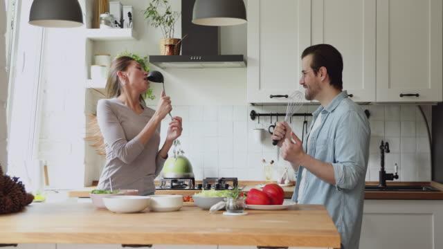 vidéos et rushes de couples utilisant des ustensiles de cuisine comme des microphones chantant la danse de chanson à l'intérieur - insouciance