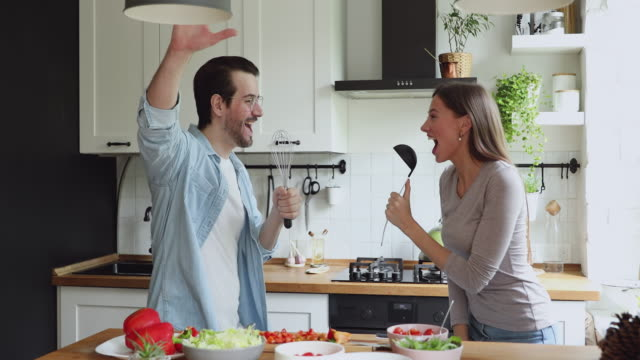 Couple using kitchen utensils like microphones singing song on kitchen Young couple in love distracted from salad preparation listen music use ladle and beater like mics sing song moving feels carefree. Funny routine, romantic date, happy homeowners first dinner together kitchen utensil stock videos & royalty-free footage
