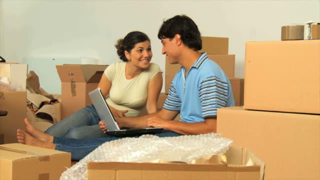 DOLLY DE LA HD : Couple à l'aide d'un ordinateur portable dans la nouvelle maison - Vidéo