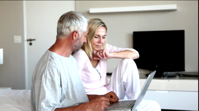 Couple using laptop together and chatting Couple using laptop together and chatting in bedroom 50 54 years stock videos & royalty-free footage