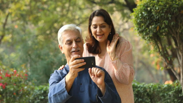 Couple using mobile phone for video call Happy senior couple using mobile phone for video call at park indian subcontinent ethnicity stock videos & royalty-free footage
