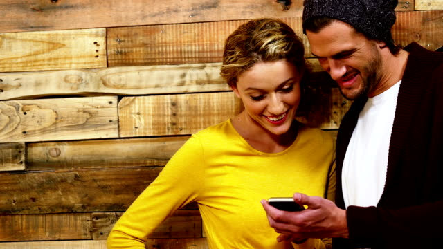 Couple using mobile phone in café video