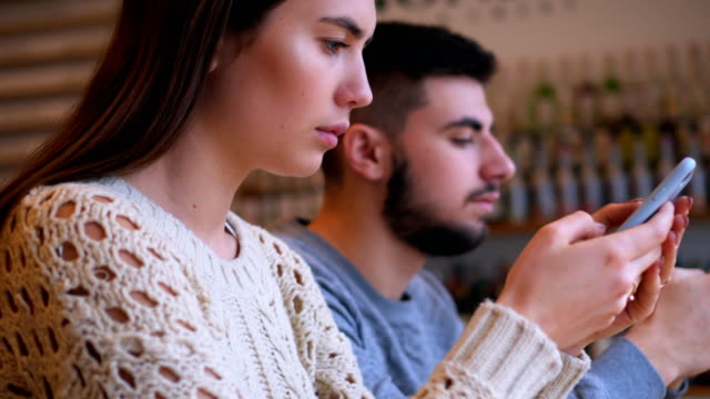 Couple using phones while ignoring each other at cafe Panning footage of couple using phones while ignoring each other at cafe ignoring stock videos & royalty-free footage