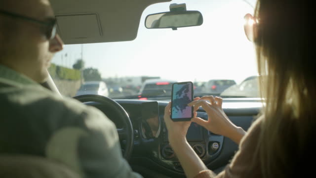 vídeos de stock e filmes b-roll de couple using smartphone in car - portugal map