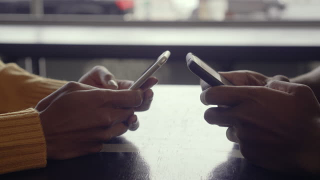 Couple using their mobile phones in cafe