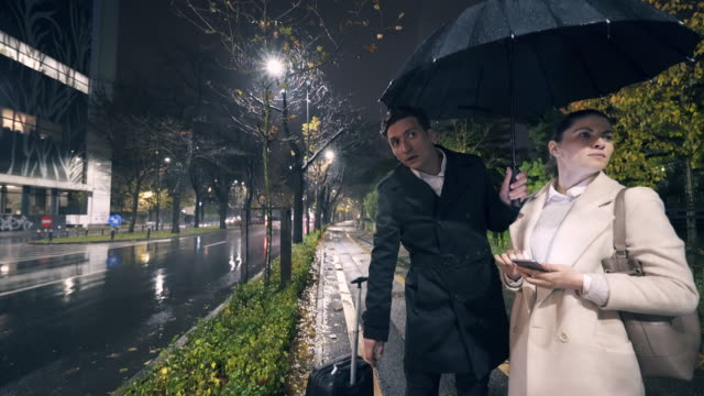 Couple waiting for taxi in a rainy night. video