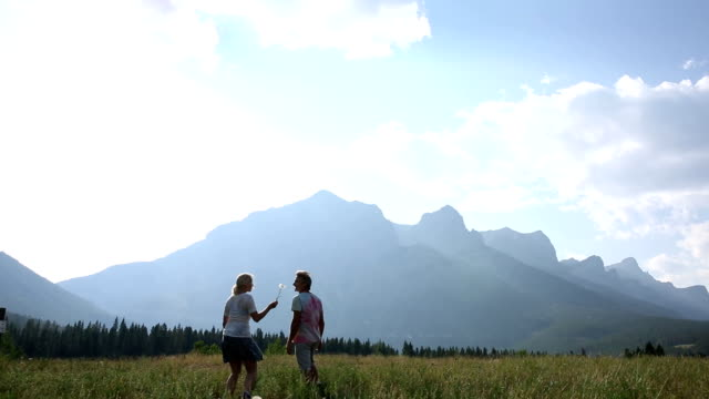 Couple walk across mountain meadow at sunrise video