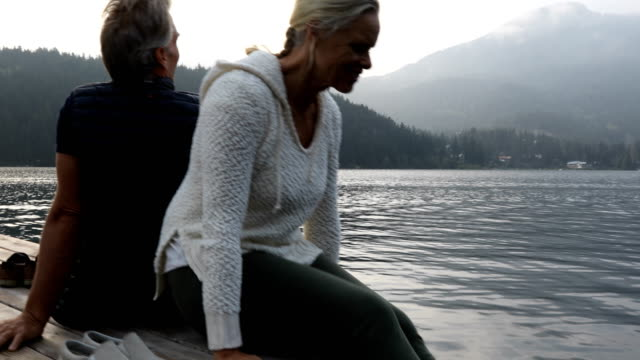Couple walk along dock at sunrise Mature couple walk out onto lake shore dock at sunrise with distant mountain panorama behind. Whistler, BC back to back stock videos & royalty-free footage