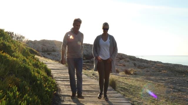 vídeos de stock e filmes b-roll de couple walk along wooden boardwalk, talking - 55 59 anos