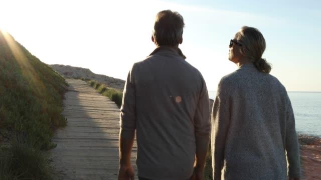 couple walk along wooden boardwalk, talking - cinquantenne video stock e b–roll