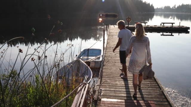 vídeos y material grabado en eventos de stock de pareja a pie a lo largo del muelle del lago de madera al amanecer - amarrado