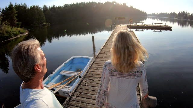 couple walk along wooden lake pier at sunrise - molo video stock e b–roll