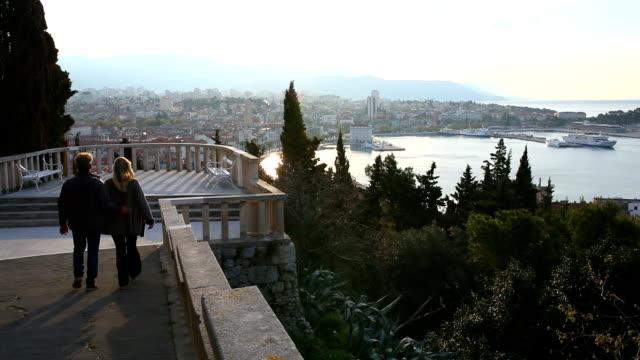 пара, пешком вниз шаги в направлении просмотра платформе, выше город - хорватия стоковые видео и кадры b-roll