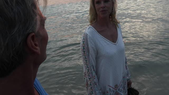 Couple walk into calm sea surf at sunrise video