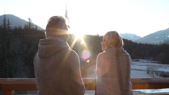 Couple walk onto deck at sunrise, above mountains