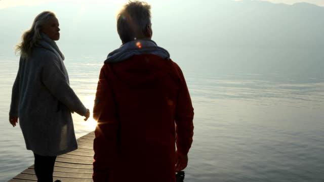 vídeos de stock e filmes b-roll de couple walk out onto atmospheric lake dock to admire tranquil mountain view - lago maggiore