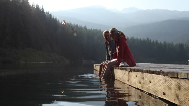 couple walk out onto pier at sunrise, in mountains - molo video stock e b–roll