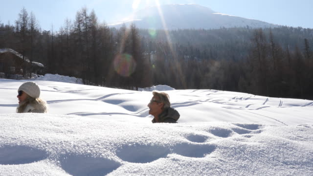 couple walk past giant snow banks on winter's day - livigno video stock e b–roll