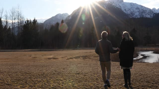 couple walk through mountain glade at sunrise - grandangolo tecnica fotografica video stock e b–roll
