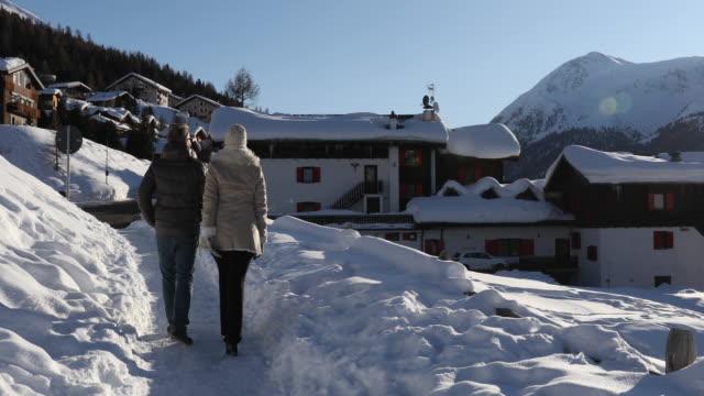 couple walk through snow towards mountain village - lombardia video stock e b–roll