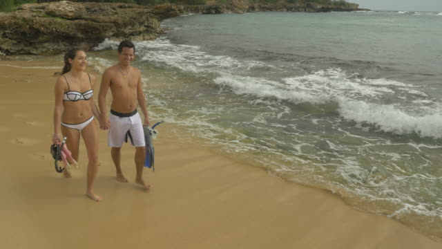 Couple walking along beach with snorkel gear in tropical climate video