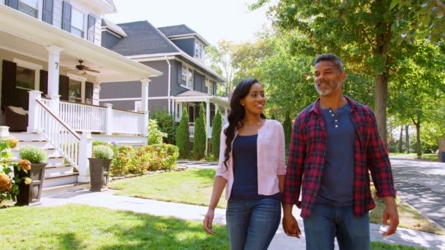 couple walking along suburban street holding hands - house video stock e b–roll