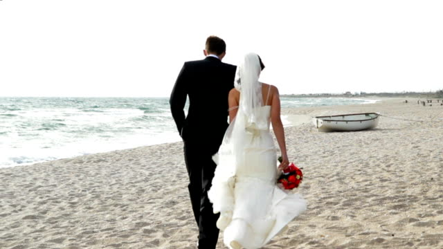 Couple walking along the beach video