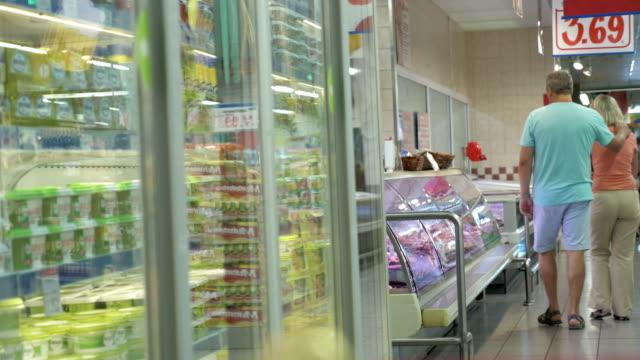 Couple Walking along the Fridges in Supermarket video