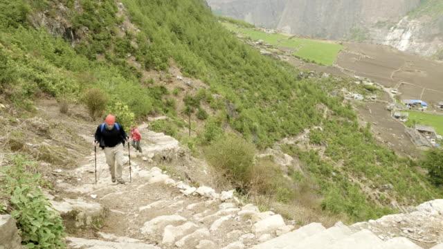 マナスル、prok、ネパールの村周辺のトレッキングを階段に沿って歩くカップル。 - ネパール人点の映像素材/bロール