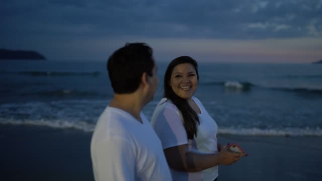 Couple walking at sunset time on the beach Couple walking at sunset time on the beach plus size model stock videos & royalty-free footage