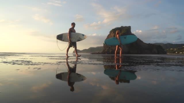 vídeos y material grabado en eventos de stock de pareja caminando de vuelta a casa después del surf. - nueva zelanda