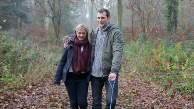 Couple Walking Dog Through Winter Woodland video