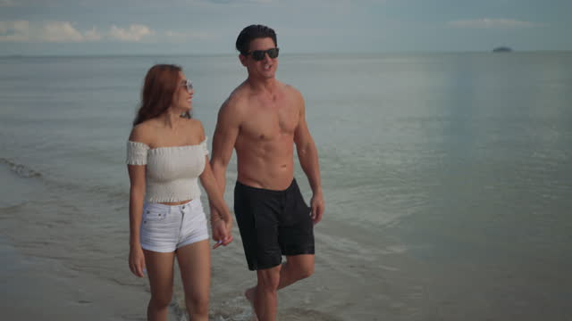 vídeos de stock e filmes b-roll de couple walking enjoy life playing and freedom beach at sunset, attractive together of man and woman traveler with dating romanric people lifestyle. 4k uhd. - casal jovem