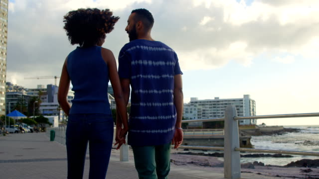 Couple walking hand in hand at beach 4k video