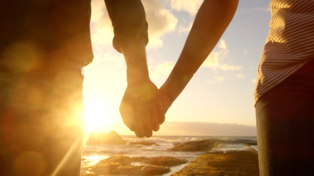 Couple walking hand in hand on the beach 4k video