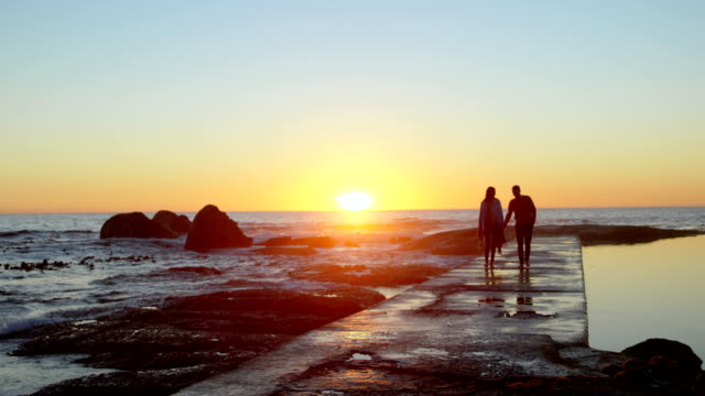 couple walking hand in hand on the pier during sunset 4k - molo video stock e b–roll