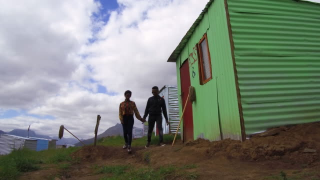 Couple walking in the township together A young African couple walk hand in hand past the township shacks western cape province stock videos & royalty-free footage