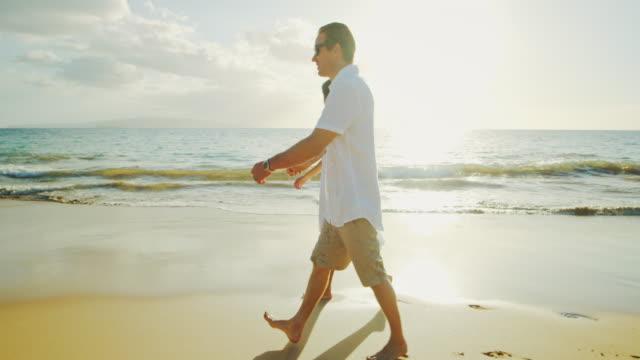Pareja caminando en la playa al atardecer - vídeo