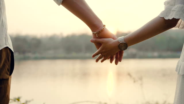 Couple Walking With Holding Hands At Sunset. Happy Couple Holding Hand and Walking on a Luxury Lake At Sunset. Thailand. young couple stock videos & royalty-free footage