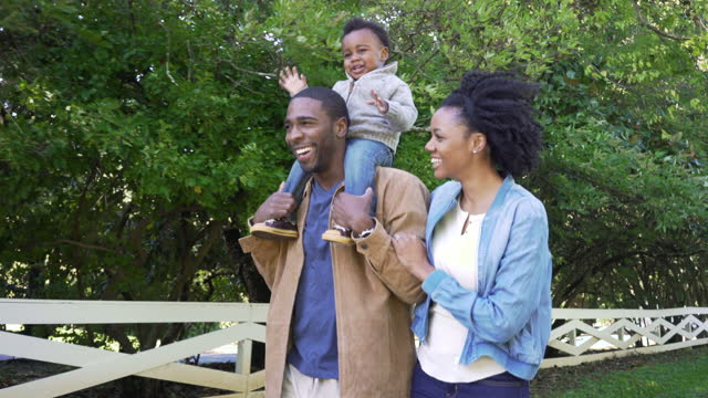 coppia che cammina con il figlio sulle spalle - piano americano video stock e b–roll