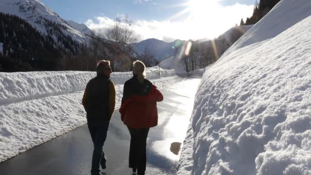paar spaziergänge entlang der verschneiten straße in richtung sonnenaufgang - eskapismus stock-videos und b-roll-filmmaterial